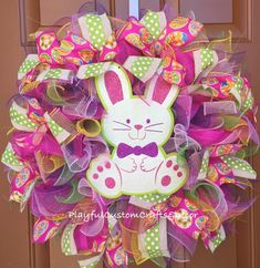 """This charming Bunny Wreath would look adorable on your front door to welcome family and friends for Easter. It is made on a 14"""" frame and measures about 24"""" across. This wreath has a white glitter bun"""