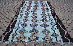 Prachtige vintage Ourika tapijt dicht geknoopt met een veld in ivoor en dikke randen van de natuurlijke ongeverfde donkerbruin wol typisch voor de Ourika tapijt weven. De prachtige compositie toont kleurrijke koorden van diamanten in een palet van warme oranje, rood, purple, groen, roze en schaduwen van mooie blauwe. Met een mooi contrasterende multicolored zigzag voering die door het donkere randen aan beide zijden van het tapijt loopt. Medium stapel, alle zachte wol. Het tapijt is in zeer…