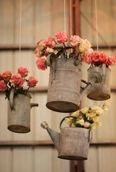 hanging old watering cans with flowers