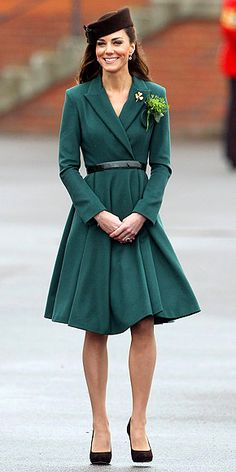 Kate Middleton in emerald wrap coat and brown pillbox hat celebrating St. Patrick's Day in Aldershot, England