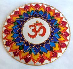 """Mandala em espelho. <br>Tamanho: 25cm de diâmetro <br>Pintura: vitral <br>Com gancho de metal, para ser pendurado na parede. <br> <br>Om (?) é o mantra mais importante do hinduísmo e outras religiões. Diz-se que ele contém o conhecimento dos Vedas e é considerado o corpo sonoro do Absoluto. O Om é o som do universo e a semente que """"fecunda"""" os outros mantras. <br>O mantra Om é a jóia principal entre os outros mantras. <br>Escutar o mantra Om é como escutar o próprio Brahman, o Ser. ..."""