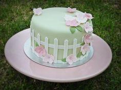Torta de 1/8 de libra con cubierta en fondant verde pastel y detalles laterales y superior en blanco y rosado