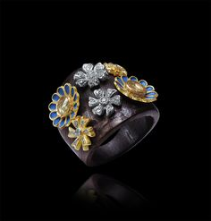 Fantastic gold and diamond flower motifs ring with enamel highlighting on a wooden base.