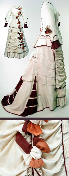 2-piece cream wool dress, 1875-77, trimmed w/chocolate brown wool & tan silk. Hip-length bodice w/high, round neck w/piping & narrow pleated frill. Centre front opening trimmed w/bows of cream & brown wool, tan silk. Brown braid trims centre back seam from neck to hem. Shaped sleeves w/single elbow bow & finely pleated wrist bands. Trained skirt of cream wool. Skirt front gathered & pleated horizontally, left front seam trimmed w/3 wool & silk bows. Manchester Galleries.