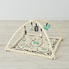 Little ones will love to explore and play on this baby activity gym designed by artist Roxy Marj. The plush mat is made from soft cotton and topped with playful animals. This set is also complete with animal rattles that are perfect for playtime. Hang the rattles on the soft bars for endless fun.
