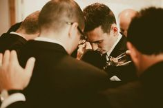 Groomsmen surrounding the groom in prayer | Lauren Apel Photography