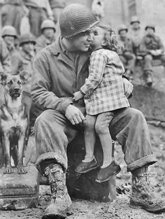 Elvin Harley of Kalamazoo, Michigan, of the 3rd Armored Division, gets a peck on the cheek from a little French girl while listening to the 9th Armored Division Band near Aboncourt in northeastern France near the Belgium border on February 14, 1945.