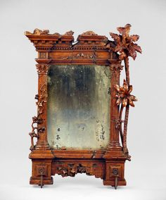 """Italian Fruitwood """"Classic Ruins"""" Mirror. The rectangular plate within pierced frame carved in """"alto relievo"""" depicting classic ruins of the Corinthian order with broken fragments cloaked by palms and verdureItaly, 19th centuryOverall dimensions: 18"""" wide x 26"""" high"""