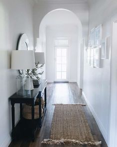 Two Bell glass lamps from MRD Home complement a dark wood sideboard in the hallway, where a runner from Freedom adds texture. Decor, Home Decor Inspiration, House, Interior, Dark Wood Sideboard, House Inspiration, White Houses, House Interior, White Walls