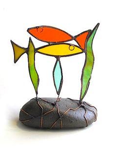 Sculptural ornament featuring stained glass fish swimming through glass seaweed and attached to an actual rock. Glass has patinated copper edging and attachments are made in copper wire. Make great gifts and work well in sets. Each fish is a unique hand crafted piece and varies in size and colour for a truly distinct and special decoration. For the best effect glass fish can be positioned on the window sill so that light illuminates through the beautiful stained glass. Come with FREE...