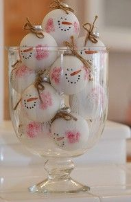 Snowman ornament party favors in a large glass container serves as centerpiece on entry table.