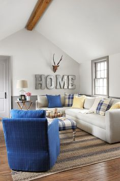To maximize every inch, Jami and Page suggested removing the radiator to bring in a generously sized, L-shaped sleeper sofa with chaise from Room and Board. A royal blue swivel chair from CR Laine matches the sofa's clean lines. An ottoman covered in a striking blue-and-cream tartan rounds out the seating options.