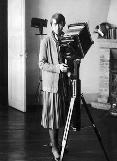 Berenice Abbott standing for a portrait, behind a view-camera, ca early 1900's.
