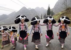 A group of Long-horn Miao (a subgroup of the Miao people) girls on the way to celebrate Miao's Tiaohua Festival (literally Dance Flower Festival)