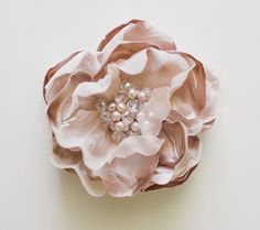 Silk satin and chiffon combine to create this beautiful flower in a dusky shade of blush. Beaded with ab glass beads and freshwater pearls.Hand pressed in the studio and attached to a metal alligator clip.One of a kind.Measures about 3 1/2 inches in diameter (about 8-9 cm).Photo by Megan Robinson.Ready to ship!