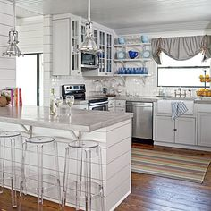 Glass-front doors on the upper cabinets and open shelving display colorful glasses and dinnerware that bring a dose of color to the mostly white room.