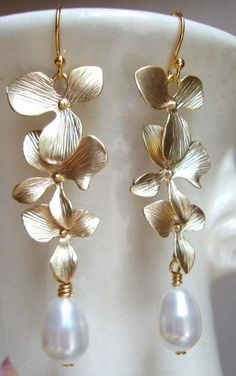 Matte Gold Orchids and Swarovski Pearls Dangle Earrings from Designs by Jocelyn. Via Diamonds in the Library.