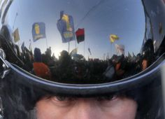 A pro-European Union rally is reflected in a police officer's helmet as he guards the way to Ukrainian President Viktor Yanukovych's country residence of Mezhygirya outside Kiev, Ukraine. Hundreds of riot police blocked approaches to Mezhygirya as protesters demanded Yanukovych's resignation over his decision to ditch a pact with the European Union in favor of closer ties with Russia. (Dec. 29, 2013) Photo Credit: AP