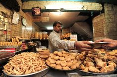 Photo: A man sells food at a stall in Old Delhi, India.