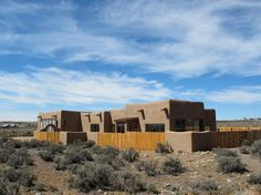 The ancient forms of pueblo revival style appear in this Taos, New Mexico, house that's full of technology and aimed at sustainability. The soft forms meet the landscape and sky with minimal intrusion, and canales pierce the parapets, stamping their trademark shadow under the bright desert sky.  houzz