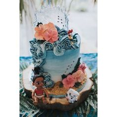 Moana birthday cake in buttercream, featuring buttercream flowers, isomalt wave and cookie crumb sand! Beautiful cake for Moana themed birthday party