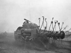 """Somewhere in Europe a Sherman tank fitted with a chain flail clears the road of mines, c. 1944 [[MORE]] """" A mine flail is a vehicle-mounted device that makes a safe path through a mine-field by. Military Engineering, D Day Normandy, Royal Engineers, Ww2 Pictures, Hell On Wheels, Sherman Tank, Military Armor, Ww2 Tanks, World Of Tanks"""