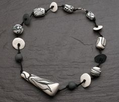 """Necklace in slate and white porcelain, satin cord, and sterling silver clasp. Necklace is 26"""" in length. Center bead measures 3.75 x 1.5 x 1.25"""""""