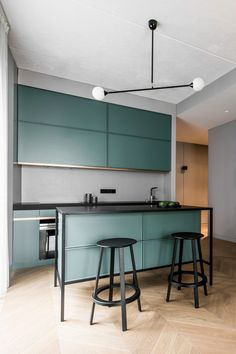 The kitchen features sleek green cabinets, a grey backsplash, a kitchen island with black framing and black stools - Modern Apartment With Laconic Design And Muted Tones