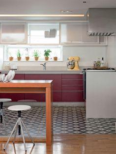 Flavio Henry e Rita Enz, da HE Arquitetura, optaram por placas da Ladrilar na cozinha. Como o ambiente é integrado, o piso foi combinado com o taco de peroba da sala. Centro de mesa da Marché Art de Vie, batedeira da Kitchenaid e vasinhos de tempero da Jardineiro Fiel.