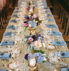 Mesa decorada com flores em tons de azul predominante