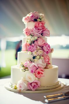 traditional tiered wedding cake with stunning pink rose waterfall