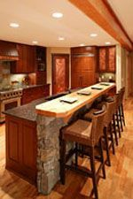 modern rustic kitchen in open floorplan, breakfast bar has stone trim and wood top. I really like the stone and the two level tops