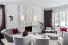 Lounge / Living Room with custom contemporary bookmatched marble slab fireplace, Ligne Roset Ploum loveseat, A Rudin barrel chairs, Giorgetti Italian sofa. Custom sheer drapery by PMK Designs