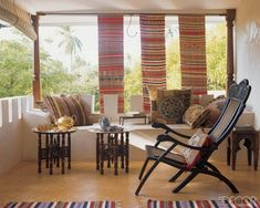 Marie-Paule Pellé enhanced the veranda of a home in Lamu, Kenya, with a Goanese chair and pillows from India and Pakistan; North African trays are set on Moroccan stools, and antique Vietnamese weavings provide shade. Photo by Pieter Estersohn for Elle Decor.