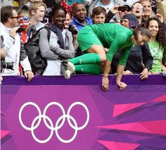 Hope Solo jumps over the boards after celebrating U.S. victory with fans. (Scott Heppell/AP)