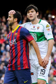 Martin Montoya of FC Barcelona jokes with Cristian Sapunaru of Elche FC during the La Liga match between FC Barcelona and Elche FC at Camp Nou on January 5, 2014 in Barcelona, Catalonia.