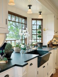 gorgeous kitchen with soapstone or black granite counters, white cabinets, oil rubbed bronze pulls and dark wood paned windows.