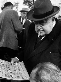 Alfred Eisenstaedt - Man smoking cigar while examining stamps at stamp market on Avenue Matignon, Paris, 1963.