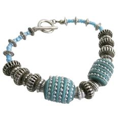 Price $9.49 Kashmiri beads are the focal point of this dramatic bracelet. Turquoise Blue Kashmiri Beads wrapped with Silver Beads Bali Spacers & Glass Beads Bracelet. Kashmiri beads is made of polymer clay mixed with hardener & resin hand decorated with faceted blue glass beads. This bracelet is Combination of fashionable stylish chic & with vibrant color beautiful handmade bracele sparkles with every movement making it a terrific gift to give yourself or someone special.