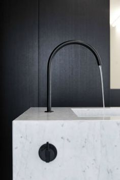 Black kitchen faucet marble counters and black cabinets.