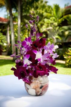 Signature #orchid centerpiece with seashell-filled vase