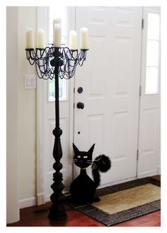 DIY Candelabra - A re-purposed chandelier, lamp, and pvc pipe are painted, and embellished to create a chic piece of macabre decor.