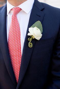 Brides.com: . A classic white boutonniere comprised of a single overblown ranunculus created by Island Ambiance.
