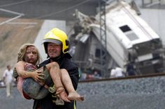 A SURVIVOR: A firefighter carried a young victim from the wreckage of a train crash near Santiago de Compostela, Spain, Wednesday. At least 80 people were killed and 140 were injured in Spain's worst train tragedy since the 1940s. Excessive speed on a curve is being investigated. (Xoan A. Soler/Monica Ferreiros/La Voz de Galicia/Reuters)