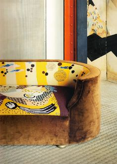 brown velvet sofa with curved back and yellow, white, blue and aubergine upholstery (@ La Maison Verre)