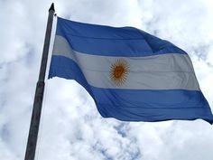 Éste es un bandera de Argentina. Los colores son azul y blanco con un sol amarillo en el centro.