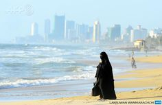 SRI LANKA, Colombo : A Sri Lankan Muslim woman walks on the beach in Colombo on September 26, 2013. Sri Lanka's youth population aged 10 to 19 make up some 15 percent of its 20 million people. AFP PHOTO/LAKRUWAN WANNIARACHCHI