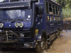 Aminah takes the plunge through a mudbath in eastern Overland Truck, Sierra Leone, West Africa, Trucks, Truck