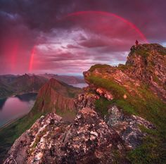 "Photography Week : Senja Sky Bridge by Daniel Kordan  ""This was taken on Senja Island, Norway, around midnight last summer. The weather changed quickly with dramatic rain clouds one side and the low sun opposite, creating this one-coloured rainbow, which is red due to the red light from the sun."""