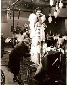 Kay Francis being fitted. Good view of a working movie set